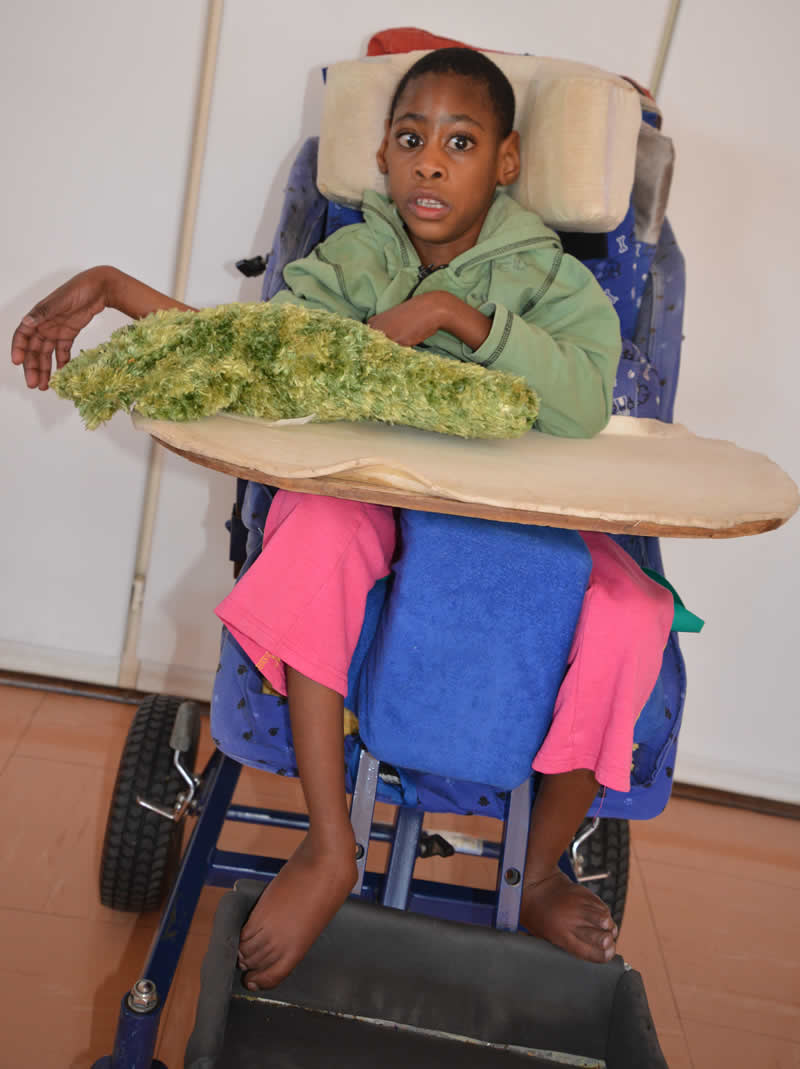 Disabled child supported in wheelchair